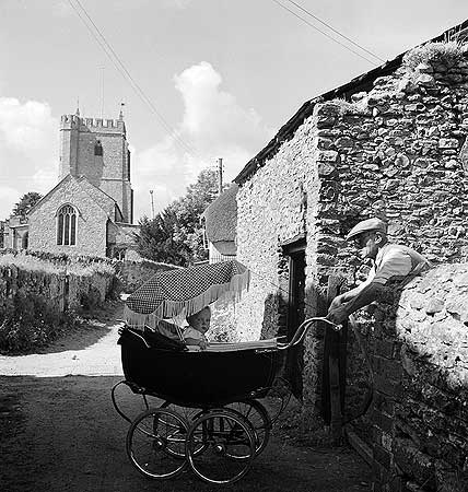 John Gay (1955 - 1965) A village scene showing a man with a flat cap leaning over a gate at Craven Cottage, Culmstock, to rock a baby in a pram, with All Saints' Church behind