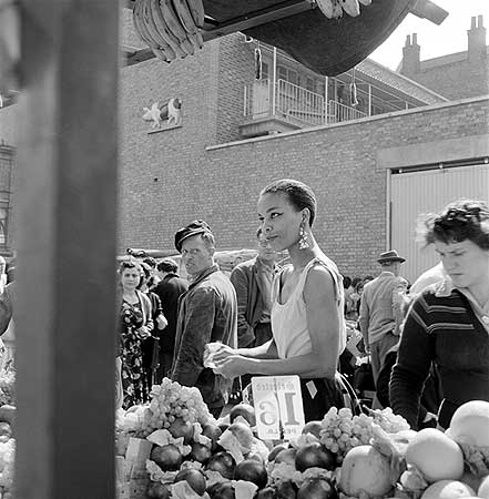 a-woman-buys-fruit-at-a-stall-in-a-north-london-street-market-photographer-john-gay-date-taken-1946-1959