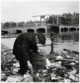 Emmy Andriesse (1945) Man scavenging, with the Magere Brug (Skinny Bridge) in the background