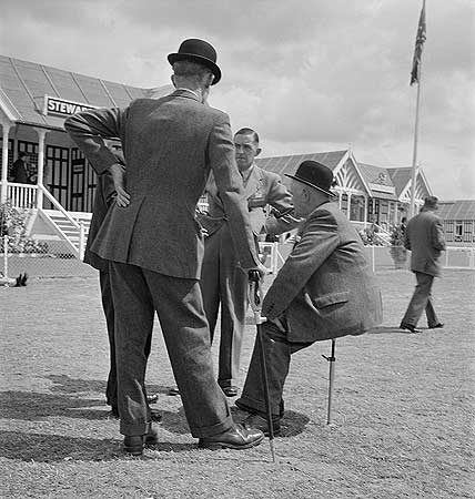 view-of-a-group-of-officials-talking-one-seated-on-a-shooting-stick-outside-the-stewards-building-at-the-royal-show-windsor-photographer-john-gay-date-taken-jul-1954