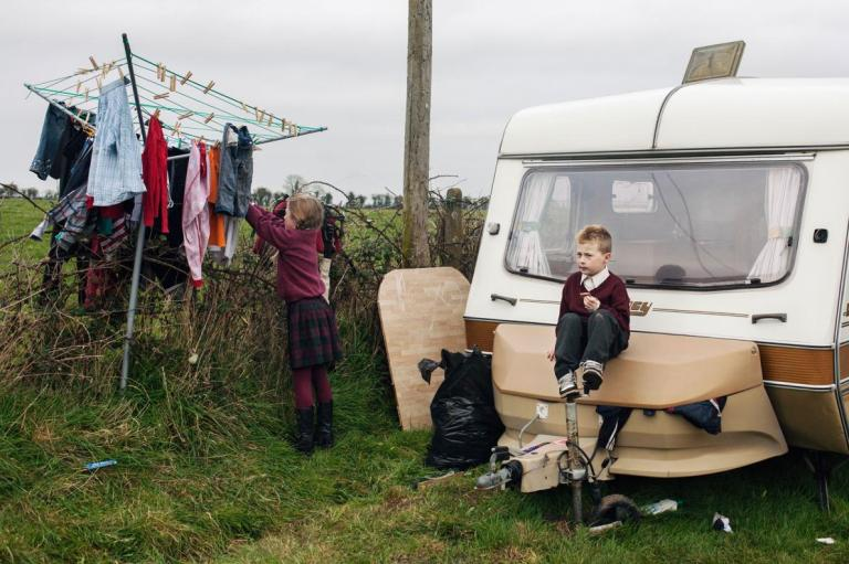 after-coming-back-from-school-in-county-kildare-james-sits-on-a-camper-bumper-while-his-sister-hangs-clothes