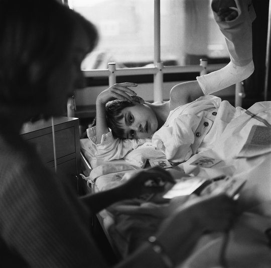 Volunteer UVV (Union of Volunteers) with child in hospital, 1964