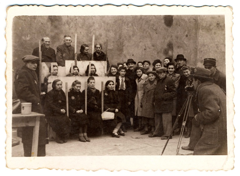 Photo attributed to Mendel Grossman showing Henryk Ross photographing identification cards for the Jewish Administration, Statistics Department, in 1940. (Courtesy, Museum of Fine Arts,
