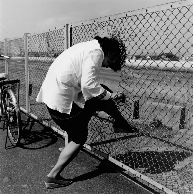 Woman passing through wire netting