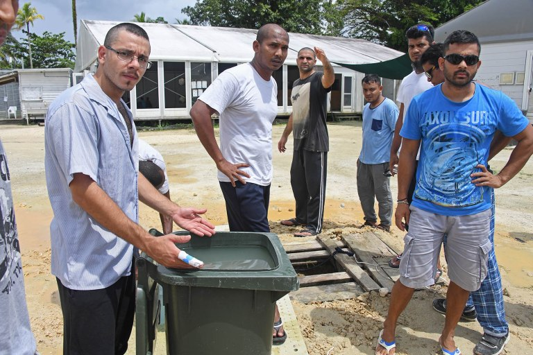 Asylum seekers are collecting water from a dirty makeshift well and filling rubbish bins
