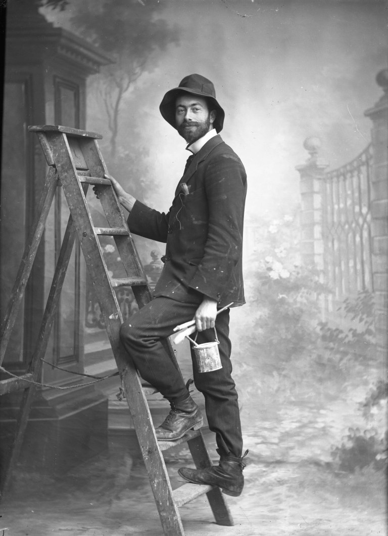 David Knights-Whittome Knights-Whittome, posed in the studio 'painting_ his backdrops. n.d. Print, from glass negative (?) Sutton Local Studies & Archives Centre, Sutto