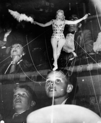 Weegee (January 1, 1950) Double exposure of circus fans watching a tightrope walker in action. Gelatin silver print 8 x 8 1:8 inches.