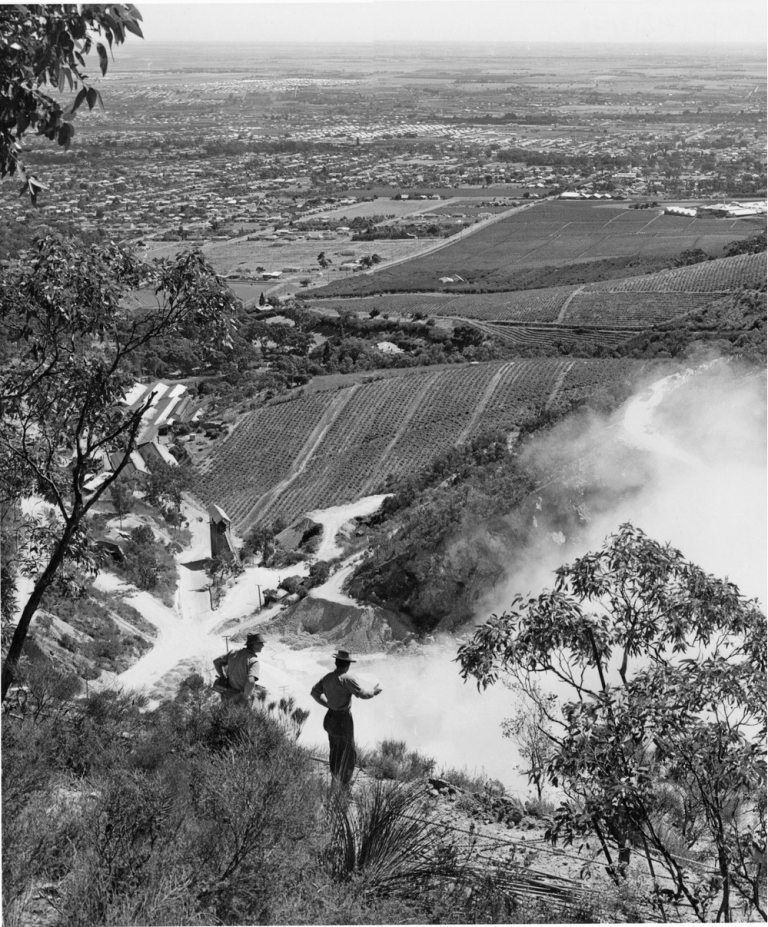 A charge is fired at the Stonyfell Quarries in the Hills above Adelaide. Looking out over Stonyfell Vineyards are Penfolds Magill Vineyards a vista of some of the N.E. suburbs is seen. The foreground quarrymen are 'New Australians'.