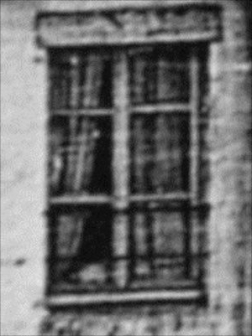 Detail from Daguerre's Boulevard du Temple showing what could be a child peering through a window in the foreground building.