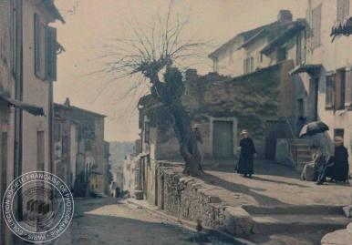 [Ville ou village, petite place, arbre], Antonin PERSONNAZ, Entre 1907 et 1936. - 1 photographie positive transparente: verre autochrome, couleur; 9 x 12 cm