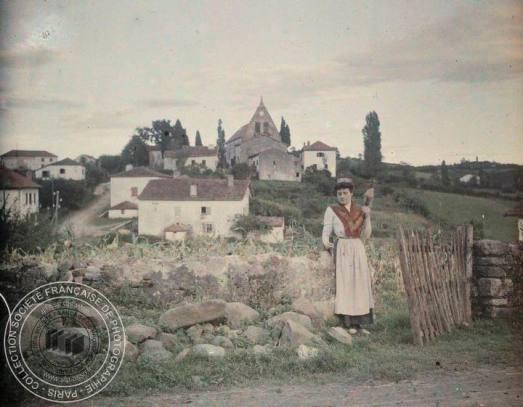 [Femme en costume folklorique sur un chemin devant un village voir 8A8], Antonin PERSONNAZ, Entre 1907 et 1936. - 1 photographie positive transparente: verre autochrome, couleur; 9 x 12 cm